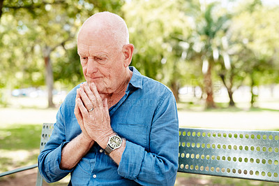 Buy stock photo Shot of a senior man sitting with his hands clasped on the park bench