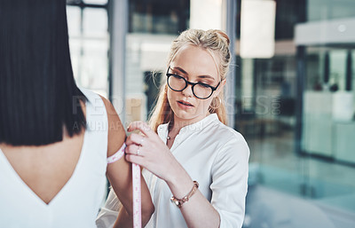 Buy stock photo Shot of a fashion designer taking her client's measurements in her workshop