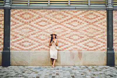 Buy stock photo Full length shot of an attractive young woman standing against a wall and using her cellphone during a vacation