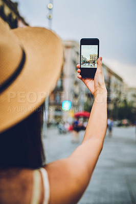 Buy stock photo Rearview shot of an unrecognizable woman standing alone and taking a picture of the city with her cellphone