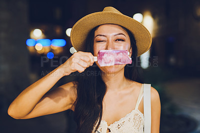Buy stock photo Cropped shot of an attractive young woman standing and playfully holding an ice lolly during late night sightseeing in Spain