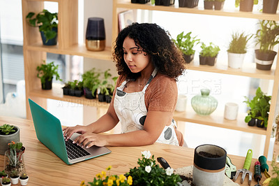 Buy stock photo High angle shot of an attractive young female botanist working on a laptop in her florist