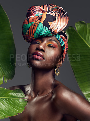 Buy stock photo Studio shot of a beautiful young woman wearing a traditional African head wrap against a leafy background