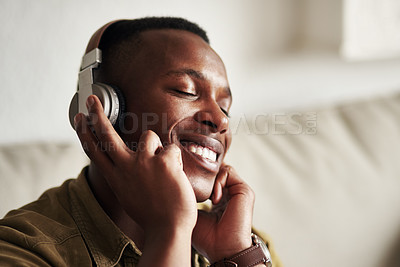 Buy stock photo Cropped shot of a handsome young man smiling with his eyes closed while listening to music on his headphones at home