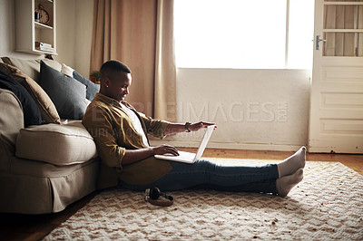 Buy stock photo Full length shot of a handsome young man using a laptop while sitting on the floor in his living room at home