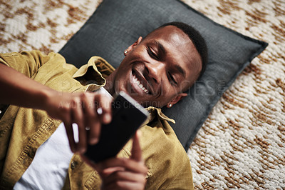 Buy stock photo High angle shot of a handsome young man smiling while using a smartphone while lying on the floor in his living room at home