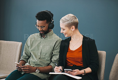 Buy stock photo Shot of two young businesspeople sitting in line while waiting for their interviews