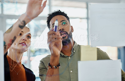 Buy stock photo Cropped shot of two young businesspeople brainstorming ideas on a glass wall
