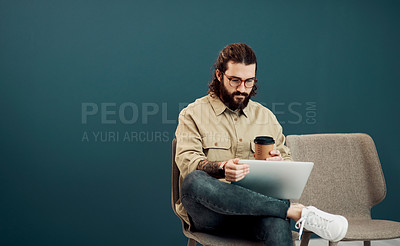 Buy stock photo Shot of a handsome young businessman drinking coffee while using a digital tablet in a waiting area