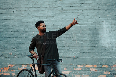Buy stock photo Shot of a young creative businessman posing with his thumbs up while traveling with his bicycle outside in the city