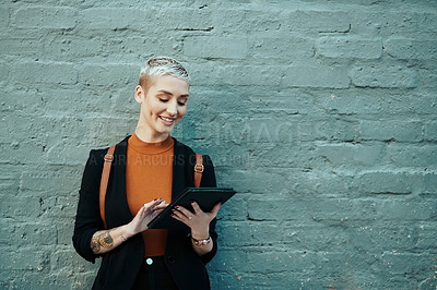 Buy stock photo Shot of an attractive young creative businesswoman using a digital tablet while standing against a grey wall outdoors