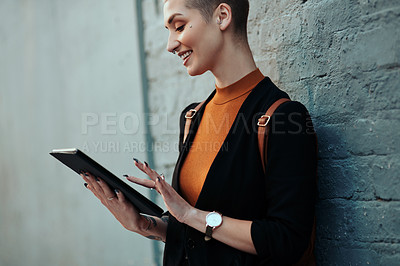 Buy stock photo Cropped shot of an attractive young creative businesswoman using a digital tablet while standing against a grey wall outdoors