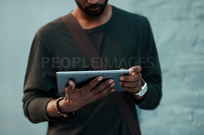 Buy stock photo Cropped shot of an unrecognizable creative businessman using a digital tablet outside in the city