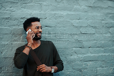 Buy stock photo Shot of a handsome young creative businessman talking on his cellphone outside in the city