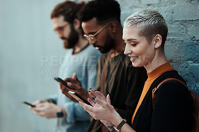 Buy stock photo Shot of an attractive young creative businesswoman using her cellphone while standing alongside her colleagues against a grey wall outdoors