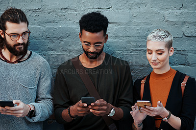 Buy stock photo Shot of a group of young creative businesspeople using their cellphones while standing against a grey wall outdoors