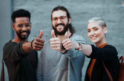 Buy stock photo Portrait of a group of young creative businesspeople posing with their thumbs up outside in the city