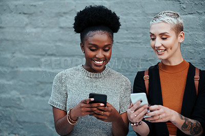 Buy stock photo Shot of two attractive young creative businesswomen using their cellphones while relaxing outside in the city