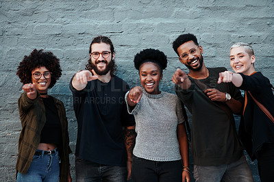 Buy stock photo Portrait of a group of young creative businesspeople pointing towards the camera while standing together outside in the city