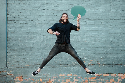Buy stock photo Full length shot of a handsome young creative businessman jumping while holding a speech bubble outdoors in the city