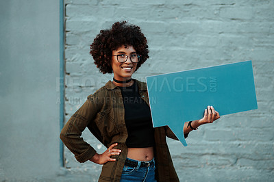 Buy stock photo Portrait of an attractive young businesswoman holding a speech bubble outdoors in the city