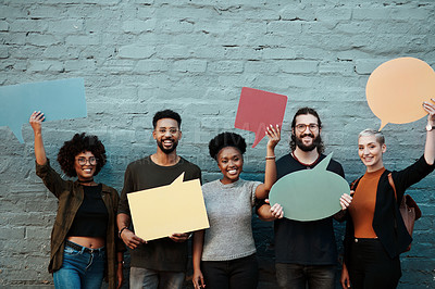 Buy stock photo Portrait of a group of young creative businesspeople holding up speech bubbles while posing together outside in the city
