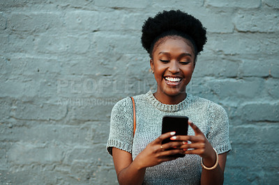 Buy stock photo Shot of an attractive young creative businesswoman using her cellphone while standing against a grey wall outdoors