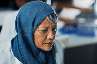 Buy stock photo Cropped shot of an attractive mature female scientist working on a computer in a laboratory while dressed in hijab