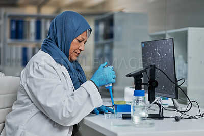 Buy stock photo Cropped shot of an attractive mature female scientist using a dropper in a laboratory while dressed in hijab