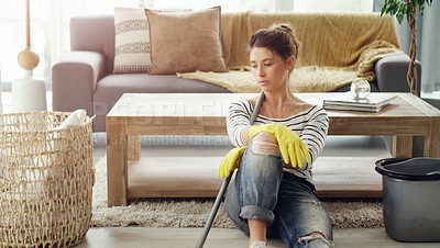 Buy stock photo Shot of a young woman taking a break from her chores at home