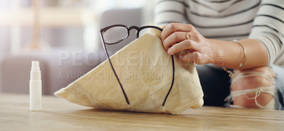 Buy stock photo Cropped shot of an unrecognizable woman cleaning her reading glasses at home