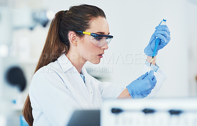 Buy stock photo Cropped shot of a focused young female scientist wearing protective glasses while pouring a test sample into a vile inside of a laboratory