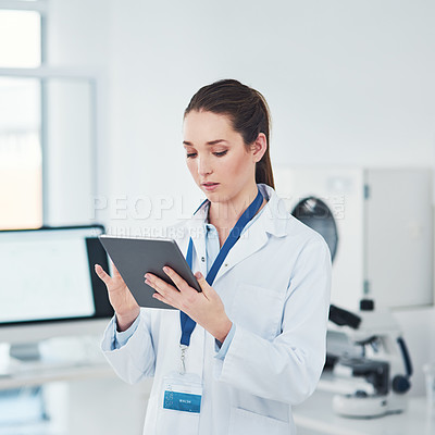 Buy stock photo Cropped shot of a focused young female scientist browsing on a digital tablet inside of a laboratory during the day