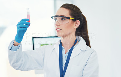 Buy stock photo Cropped shot of a focused young female scientist holding up a vile of blood and observing it inside of a laboratory during the day