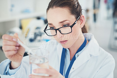 Buy stock photo Cropped shot of a focused young female scientist mixing chemicals together at their desk inside of a laboratory