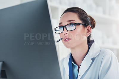 Buy stock photo Cropped shot of a focused young female scientist working on a computer inside of a laboratory during the day