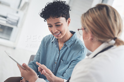 Buy stock photo Cropped shot of an attractive young female doctor using a digital tablet while having a discussion with a female patient in her office