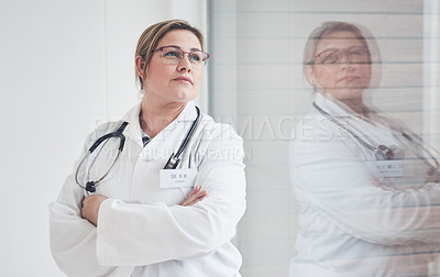 Buy stock photo Cropped shot of an attractive young female doctor looking thoughtful while standing with her arms crossed in her office
