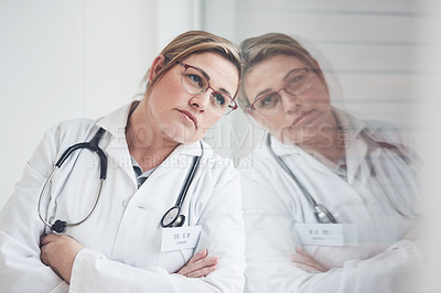 Buy stock photo Cropped shot of an attractive young female doctor looking thoughtful while leaning against the wall with her arms crossed in her office