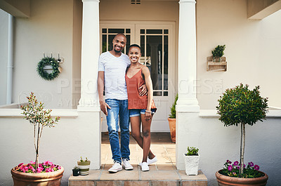 Buy stock photo Shot of a happy young couple standing on their front porch