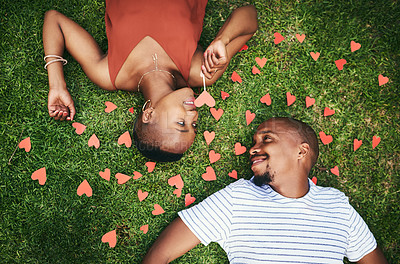 Buy stock photo Cropped shot of a young couple lying on the lawn outside