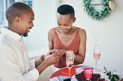 Buy stock photo Shot of a young man proposing to his his girlfriend on a romantic date