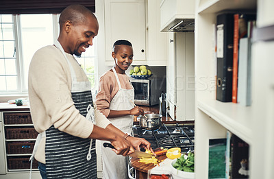 Buy stock photo Cropped shot of an affectionate young couple preparing dinner in their kitchen