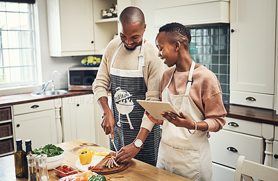 Buy stock photo Cropped shot of an affectionate young couple using a tablet while preparing dinner in their kitchen
