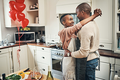Buy stock photo Cropped shot of an affectionate young couple embracing while preparing dinner in their kitchen