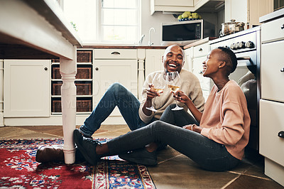 Buy stock photo Full length shot of an affectionate young couple enjoying a glass of wine while preparing dinner in their kitchen