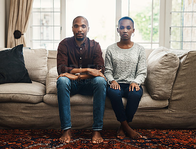 Buy stock photo Full length shot of a young couple looking serious and sitting alongside each other on a sofa at home