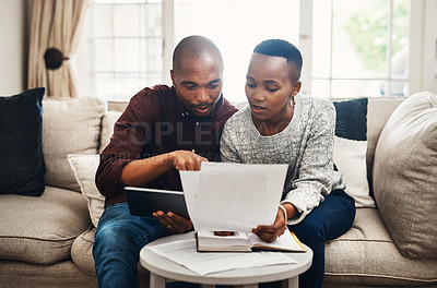 Buy stock photo Shot of a young couple using a digital tablet while  going over their bills and finances at home