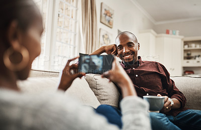 Buy stock photo Shot of a handsome young man posing for the camera while his girlfriends takes pictures of hime with her cellphone at home