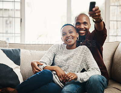 Buy stock photo Shot of a happy young man changing the tv channel whiles spending time with his girlfriend at home